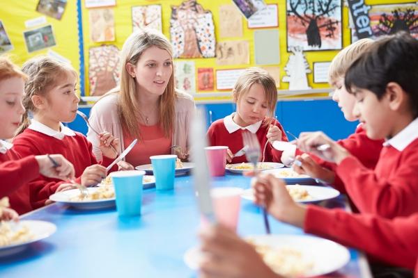 School children eating with teacher